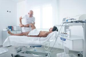 Fisioterapista che pratica un massaggio sportivo con tecarterapia