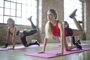 Tre ragazze che fanno ginnastica su un tappetino in palestra
