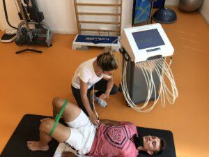 Paziente sdraiato sul pavimento di una palestra con una fisioterapista